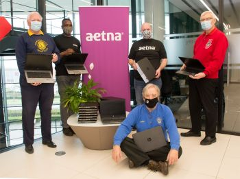 Members of the local Lions Club with mdembers of the IT Team at Aetna International at the donation of hundreds of computer devices for local schools